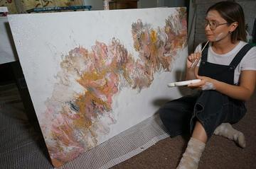 Megan sat in front of a painted board, brush in hand, paint on face, contemplating the next brush stroke